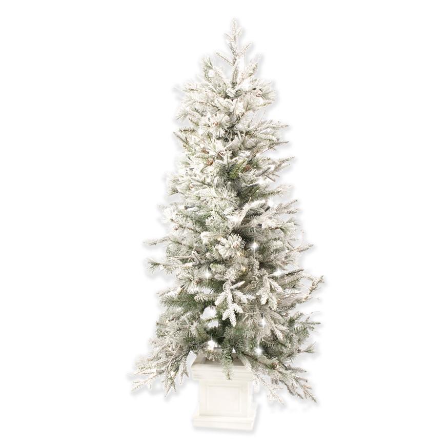 Пушистая заснеженная елка в белой подставке