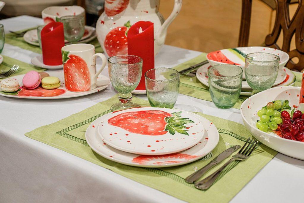 Белая скатерть уравновешивает игру красок, а салатовые салфетки не позволяют сливаться белизне текстиля и керамики